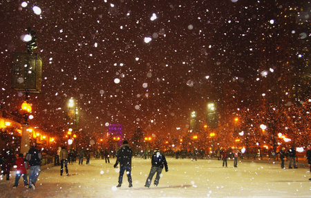 People enjoying ice skating during snowy night in Chicago. Stok Fotoğraf