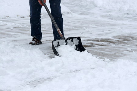 Man shoveling snow on driveway during a heavy snowfall. Close up composition.