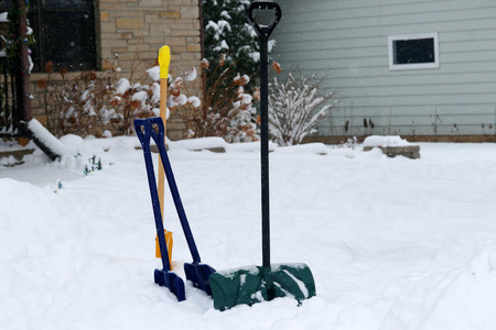 Group of colorful shovels in a snowdrift on a private house front yard ready for outdoor cleaning on a snowy background during blizzard day.