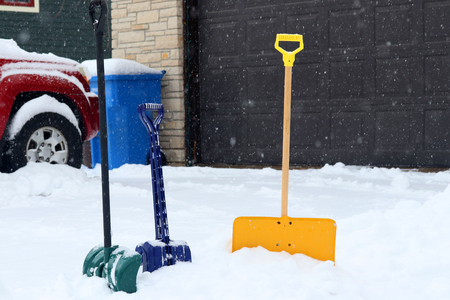 Three colorful shovels in snowdrift on a foreground along covered by fresh snow driveway and garage door on a snowy background. Stock Photo