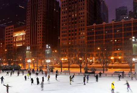 People in motion enjoying ice skating during beautiful winter night in Chicago downtown. Urban architecture background, big city life concept.