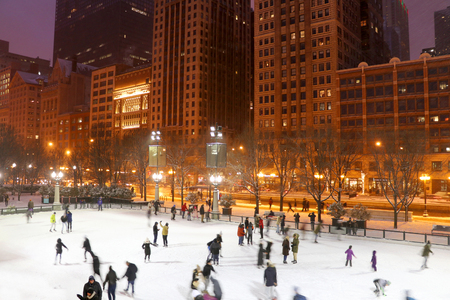 People in motion enjoying ice skating during beautiful winter night in Chicago downtown. Urban architecture background, big city life concept. Chicago, Illinois, Midwest USA.
