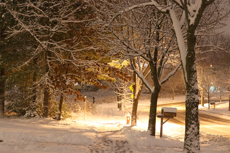 Beautiful winter evening landscape with footprints on a covered by fresh snow sidewalk and shining lanterns along a street.
