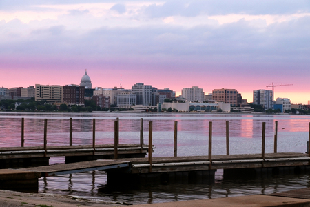 After sunset view with State Capitol building dome against beautiful colored sky from Olin Park. Wooden piers on a foreground.