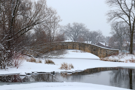 Winter snowy day landscape with an old style brick bridge during snowfall. Tenney Park in the city of Madison, the capital of Wisconsin, Midwest USA.