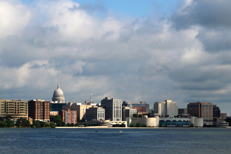 Downtown skyline of Madison, the capital city of Wisconsin, USA. Morning view with State Capitol and official buildings in sunlight against beautiful cloudy sky and lake water as seen across lake Monona. Фото со стока