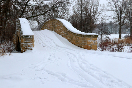 Winter snowy day landscape with a path through an old style brick bridge over the frozen water channel, covered by fresh snow with footprints on it during snowfall. Tenney Park, Madison, Wisconsin, USA.