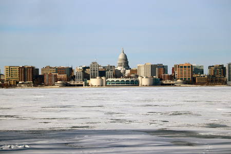 Winter day view with State Capitol building and Monona Terrace across the frozen lake Monona.