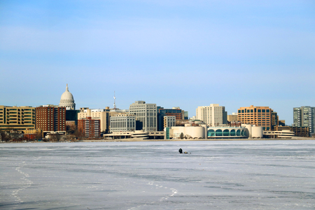Winter day view with State Capitol building and Monona Terrace across the frozen lake Monona from the Olin Park. Fisher on the ice.