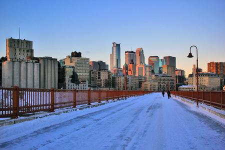 Beautiful winter morning in Minneapolis. Downtown cityscape from the Stone Arch Bridge on a skyline and skyscrapers in the rising sun light. Minnesota state, Midwest USA.