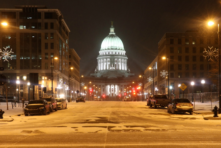 Madison, the capitol of Wisconsin downtown street view with parked cars and Wisconsin state capitol building glowing in the blizzard night. Wisconsin state, Midwest USA. Фото со стока