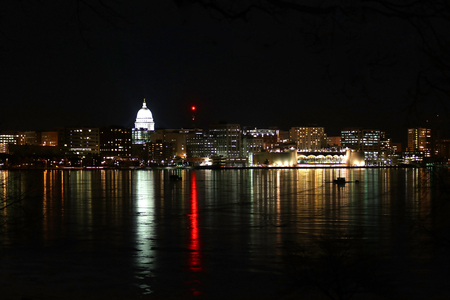 Madison downtown skyline at winter night with official buildings, Monona Terrace and capitol dome, glowing in the dark. Cityscape reflects in a frozen lake Monona.