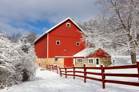 Rural landscape with red barn, wooden red fence and trees covered by fresh snow in sunlight. Scenic winter view at Wisconsin, Midwest USA, Madison area.
