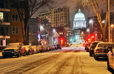 Beautiful night cityscape. Madison, the capitol of Wisconsin downtown street view with parked cars and Wisconsin state capitol building glowing in the snowy night. Wisconsin state, Midwest USA. Фото со стока