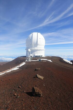 Hawaii Big Island nature background. Scenic view from mountain with observatory building, snow remains and bright blue sky. Vertical composition.