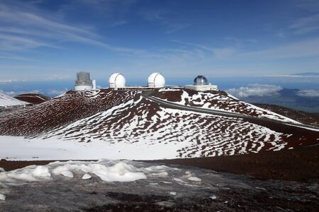 Hawaii Big Island nature background. Scenic view from mountain with paved road between observatories, snow remains and bright blue sky.