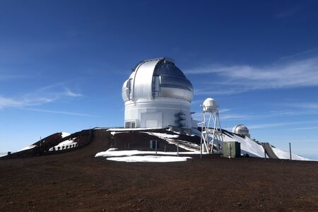 Hawaii Big Island nature background. Scenic view from mountain with observatory building, snow remains and bright blue sky.