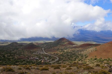 Scenic Mauna Kea landscape with paved road to summit between old craters and view on Mauna Loa in clouds.