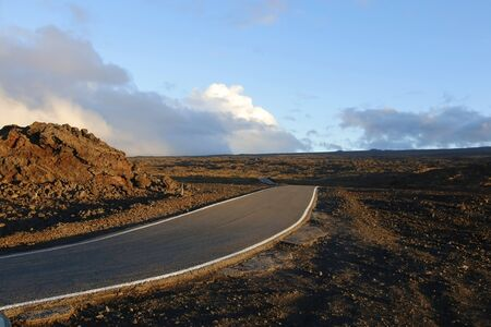 Mauna Loa landscape with paved road to the summit through lava fields during sunset.