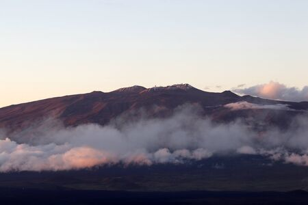 Scenic landscape with Mauna Kea peak with observatories above the clouds. Amazing view from Mauna Loa during sunset. Фото со стока