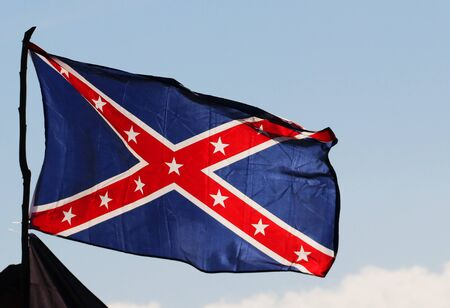Confederate rebel flag reversed colors waving in the wind against the blue sky background in Charleston, South Carolina, USA.