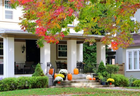 Main entrance stair and porch of the stylish house decorated for autumn holidays season, branches of the colorful tree in a foreground. Fall background. Фото со стока