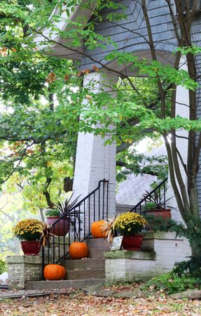 Main entrance stair and porch of the old house decorated for autumn holidays season. Halloween concept. Fall background. Vertical composition. Фото со стока
