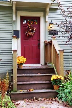 Main entrance red door, wooden stair and porch of the old house decorated for autumn holidays season. Halloween concept. Fall background. Vertical composition. Фото со стока