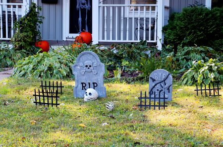 Front yard of private house decorated by fake skull, bones hands, tombstones and grates, pumpkins on the porch for a old american trick-or-treat Halloween tradition. Фото со стока