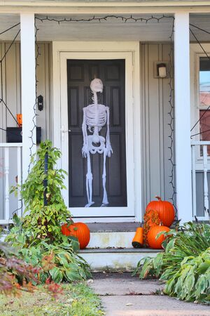 Private house front door with fake skeleton and stair with bright pumpkins decorated for an old american trick-or-treat Halloween tradition. Vertical close up composition.