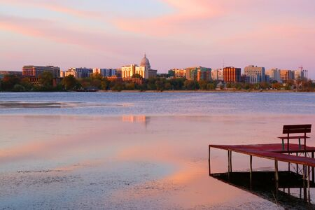 Madison downtown skyline with Wisconsin State Capitol building dome as seen from across lake Monona bay during sunset. Wooden pier and fallen leaves on water surface on a foreground. Midwest USA, Wisconsin.