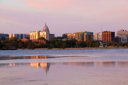 Madison downtown skyline with Wisconsin State Capitol building dome as seen from across lake Monona bay. Buildings and bright colors sky reflected in the water.
