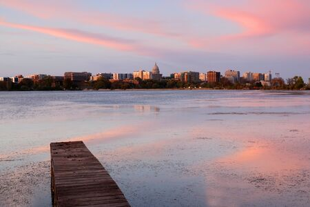 Madison downtown skyline with Wisconsin State Capitol building dome across lake Monona bay during sunset. Wooden pier and fallen leaves on water surface on a foreground. Midwest USA, Wisconsin. Stockfoto - 150297110