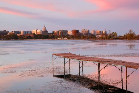 Madison downtown skyline with Wisconsin State Capitol building dome as seen from across lake Monona bay during sunset. Wooden pier and fallen leaves on water surface on a foreground. Midwest USA, Wisconsin. Stockfoto - 150296504