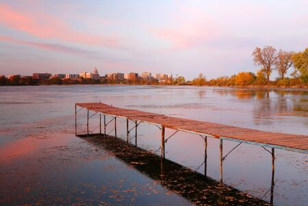 Madison downtown skyline with Wisconsin State Capitol building dome as seen from across lake Monona bay during sunset. Wooden pier and fallen leaves on water surface on a foreground. Midwest USA, Wisconsin. Stockfoto - 150296633