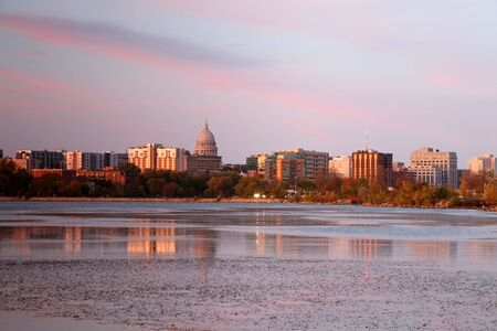Madison downtown skyline with Wisconsin State Capitol building dome as seen from across lake Monona bay. Buildings and bright colors sky reflected in the water. Фото со стока