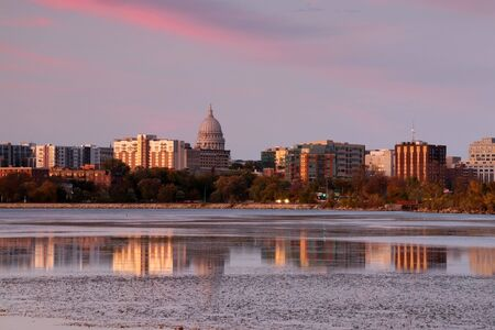 Madison downtown skyline with Wisconsin State Capitol building dome across lake Monona bay. Buildings and bright colors sky reflected in the water. Stockfoto - 150296662
