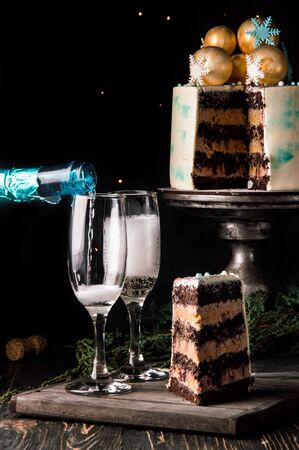 Close up. New Year celebration. ?ake in the cut. Nearby is a wooden board with a piece of sliced chocolate cake and two glasses of champagne. Dark background. Copy space.