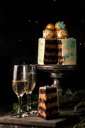 Close up. Christmas cake in the cut. Nearby is a wooden board with a piece of sliced chocolate cake and two tall glasses of champagne. Dark background with christmas lights. Copy space.