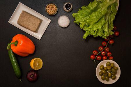 Flat lay, top view. Italian food. Plant based ingredients for vegan greek salad on black background. Copy space. Zdjęcie Seryjne