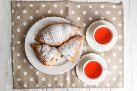 Flat lay, close up. Romantic breakfast for two. Freshly baked French croissants and berry tea. One of the croissants is cut in half. Vintage white porcelain, polka dot pastel napkin. Banque d'images