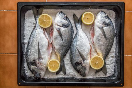 Close up. Fresh raw dorado fish laid out with lemons on salt in a baking tray. Preparing fish for roasting. Mediterranean cuisine. 写真素材