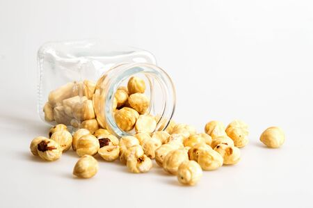 Close up, macro. A glass jar is lying sideways, a bunch of hazelnuts are scattered around it. White background. Copy space. 写真素材 - 131931625