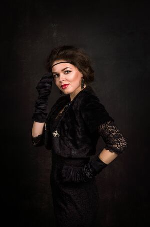 Roaring Twenties. Woman portrait in the style of Gatsby. Low key. A beautiful young woman in a black dress touches cheek with the hand on which she wears a black glove. Romantic gaze fixed on camera.