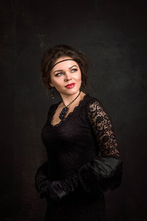 Close up. Roaring Twenties. Woman portrait in the style of Gatsby. Low key. Beautiful young woman in a black dress, satin gloves and a black fur cape. Enchanted look sent to the side.