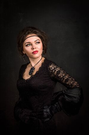 Close up. Roaring Twenties. Woman portrait in the style of Gatsby. Low key. Beautiful young woman in a black dress, satin gloves and a black fur cape. The look is directed aside.