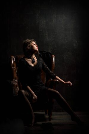 Roaring Twenties. Woman portrait in the style of Gatsby. Low key. A beautiful young woman in a black lace dress is sensually sitting in a brown leather chair. Black background. Stock Photo - 128506053