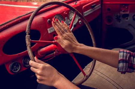 Hands of a beautiful girl holding the steering wheel of an old red car.