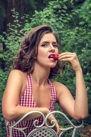 Emotional portrait. Pin-up girl sexually bites off strawberries. Sensual gaze directed into the camera. Green park on the background. Stock Photo - 127225014