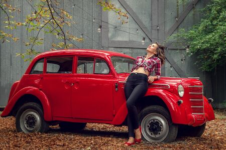 Pin-up girl in jeans and a plaid shirt is leaning on a russian red retro car. She smiles, basking in the sun.